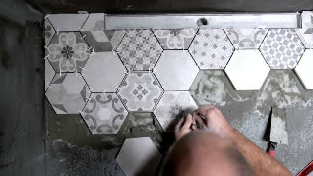 Adult mason installing tiles on the bathroom floor