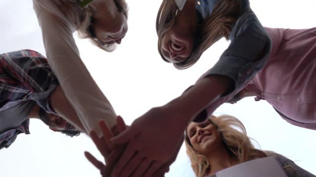 stockvideo's en b-roll-footage met volwassen mba-studenten in een huddle en vervolgens vieren met een hoge vijf - huddle