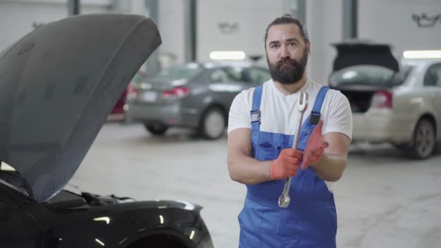 Adult mechanic standing near the car with an open hood and holding huge wrench in hands. Adult mechanic standing near the car with an open hood and holding huge wrench in hands. Bearded man in uniform fixing automobile in car repair station wrench stock videos & royalty-free footage