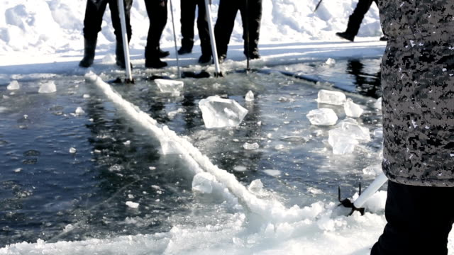 adult men use special saws for cutting ice on the extreme sailing on the frozen lake in snowy - monti urali video stock e b–roll