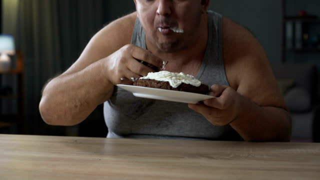 Adult overweight man gobbling cake and licking his fingers, diabetes, junk food video