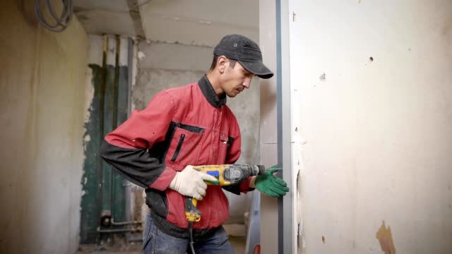 adult repairman is drilling hole in a metal profile by electric drill inside building on a construction site video