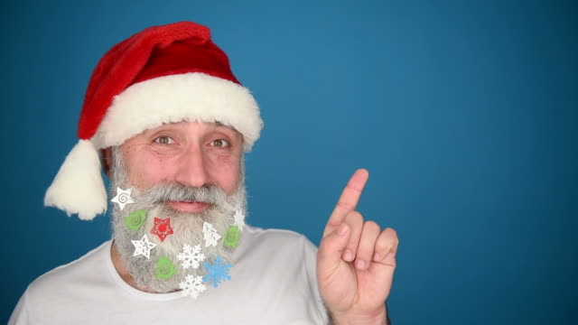Adult senior man showing a copy space and showing the thumb in the Santa Claus hat on a blue background video