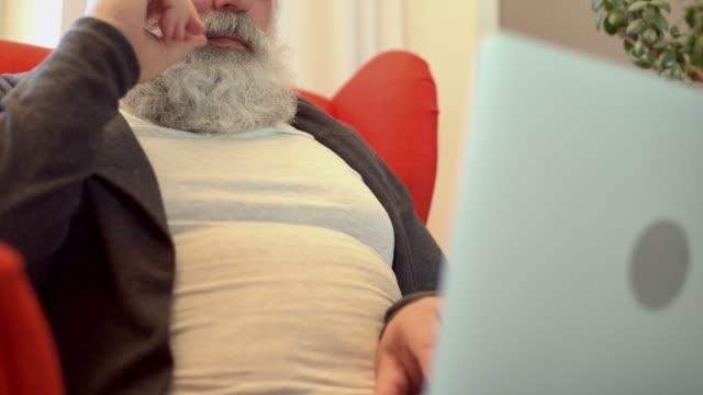 adult senior man med grått skägg arbetar på en bärbar dator - endast en medelålders man bildbanksvideor och videomaterial från bakom kulisserna