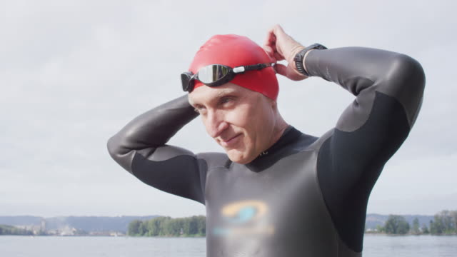 adult senior triathlete preparing for a swim - 50 59 lat filmów i materiałów b-roll