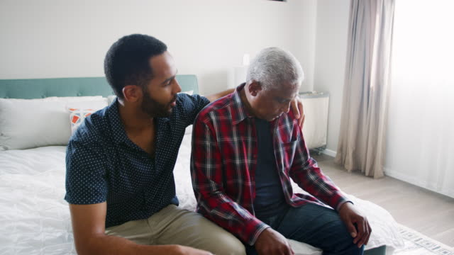 Adult son comforting depressed senior father sitting in bedroom at home - shot in slow motion