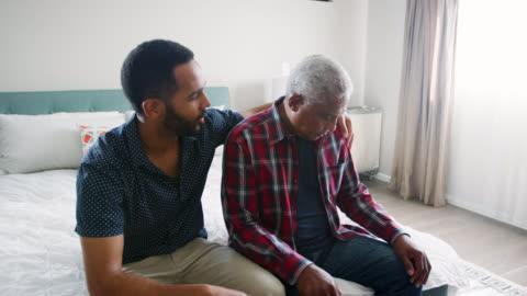 figlio adulto confortante padre anziano depresso seduto in camera da letto a casa - girato al rallentatore - accudire video stock e b–roll
