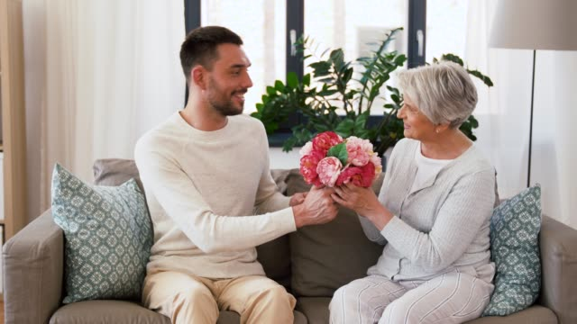 adult son giving flowers to senior mother at home