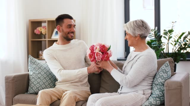adult son giving flowers to senior mother at home - vídeo