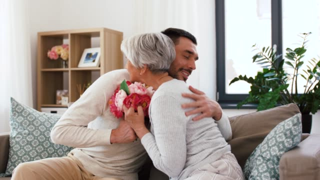 adult son giving flowers to senior mother at home family, mother's day and birthday concept - smiling adult son giving flowers and hugging his senior mother at home mothers day stock videos & royalty-free footage