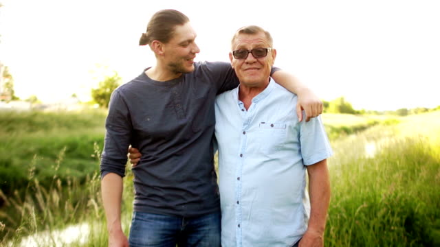 Adult son hugging his senior dad, on the river bank. Two generations, male conversation, male friendship, father's day. Elderly man looks at the camera video