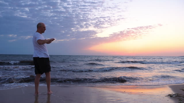 Adult sportsman warming up arms on seashore in the morning Adult sportsman warming up arms on seashore in the morning, rear view. Athletic man warming up and exercising on beach at sunrise over sea with copy space mental wellbeing stock videos & royalty-free footage
