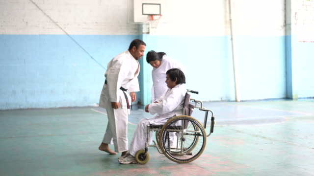 Adult teacher teaching parakarate a young adult people with disability