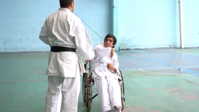 Adult teaching to a latin man in a wheelchair practicing karate poses