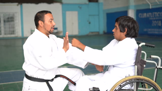 Adult teaching to a latin man in a wheelchair practicing parakarate poses