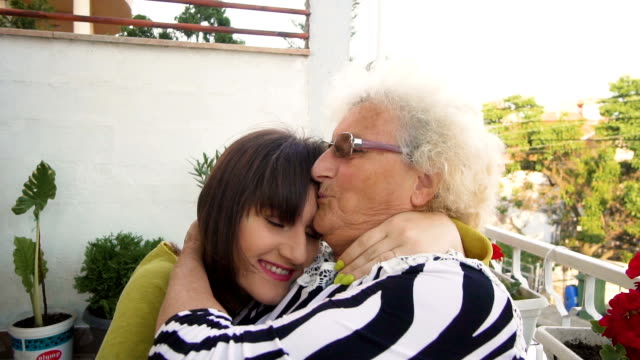 Adult teenager daughter kiss and embrace her smiling happy senior mother outdoor, SLOW MOTION