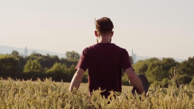 Erwachsenen zu Fuß durch schöne Weizen Feld Holding Skateboard mit Stadt im Hintergrund - Schuss auf rot – Video