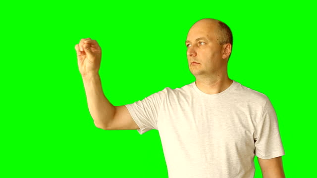 Adult white caucasian man gestures with green screen. Draw line touch tap virtual screen. Upper half close-up shot. Male in white t-shirt. Clip with Premultiplied matted Alpha Channel. video