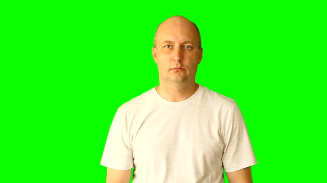 Adult white caucasian man gestures with green screen. Looking up thinking threaten fist hand finger. Upper half close-up shot. Male in white t-shirt. Clip with Premultiplied matted Alpha Channel. video