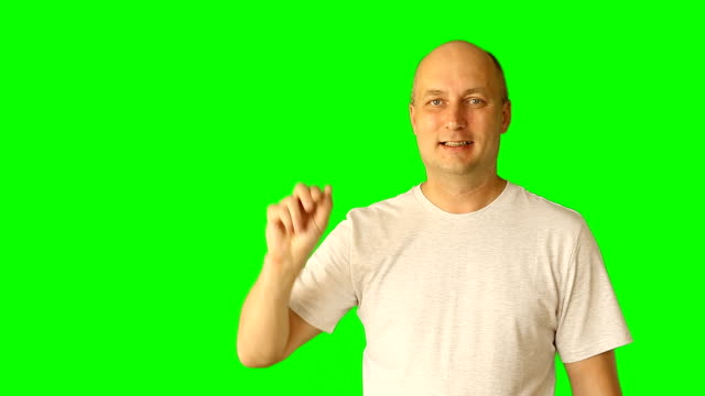 Adult white caucasian man laughing and make gestures with green screen. Draw line touch tap virtual screen. Upper half close-up shot. Male white t-shirt. Clip with Premultiplied matted Alpha Channel. video