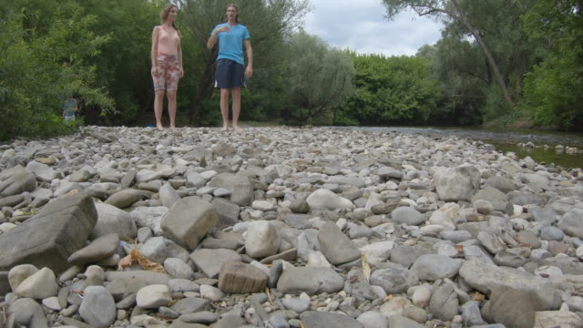Adult Woman and Man Standing on Pebble Riverbank Barefoot