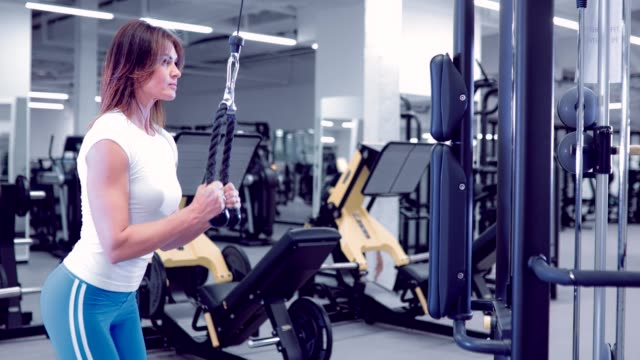 Adult woman doing Exercises for Tricep in fitness gym. Beautiful Woman doing triceps workout. Fitness girl doing triceps cable pushdown exercise in gym video
