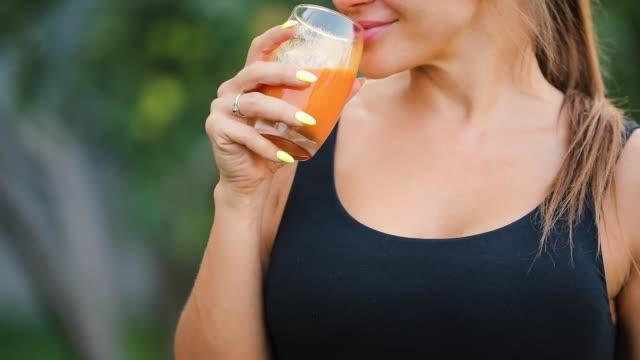 erwachsene frau trinkt orangensaft in einem garten, gesunden lebensstil-konzept - einzelne frau über 30 stock-videos und b-roll-filmmaterial