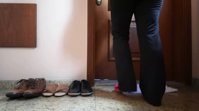 Adult woman leaving your shoes out Adult woman walking into the house wearing socks leaving shoes with other pairs outside the door as a hygiene habit shoe stock videos & royalty-free footage