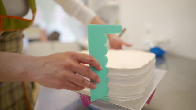 vuxen kvinna gör en tårta på en köksbänken - hemmagjord bildbanksvideor och videomaterial från bakom kulisserna