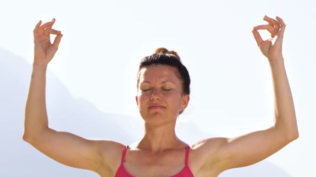 Adult woman meditating in mudra posture outdoors