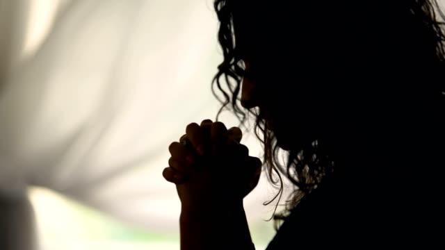 adult woman reading god's prayer crossing fingers in silhouette, camera zoom - modlić się filmów i materiałów b-roll