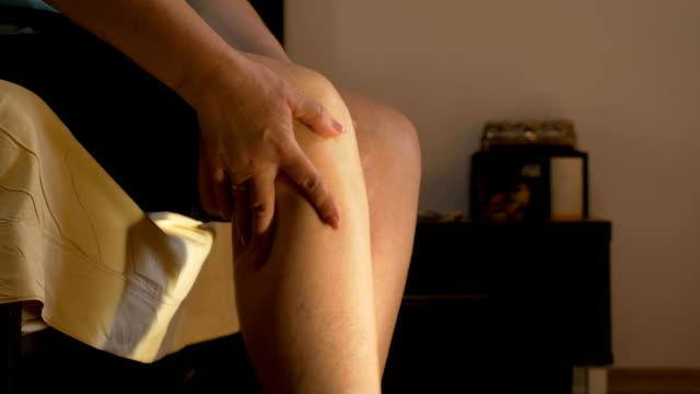 vídeos de stock, filmes e b-roll de adulta mulher sentada no quarto esfregando o joelho artrítico - perna termo anatômico