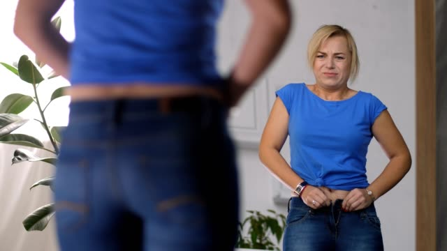 adult woman struggling to zip up too tight jeans - dbałość o ciało filmów i materiałów b-roll