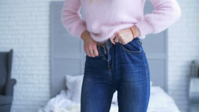 adult woman trying to zip up tight jeans at home - dżinsy filmów i materiałów b-roll