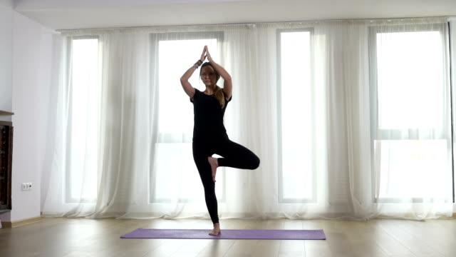 stockvideo's en b-roll-footage met volwassen vrouw opwarmen voor yoga praktijk - portait background