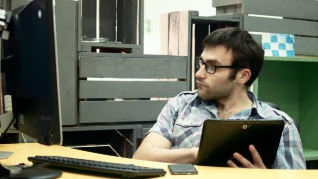 erwachsenen arbeitnehmer mit tablett und computer am arbeitsplatz - tablet mit displayinhalt stock-videos und b-roll-filmmaterial