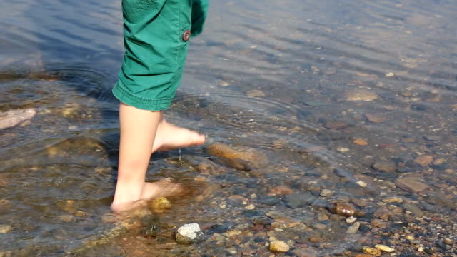 Adult's and child's feet in water video