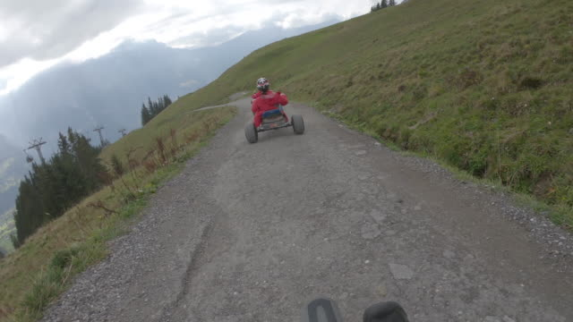 Adults descend mountain track on go carts, through alpine meadow Mountains in distance, Bern Canton go cart stock videos & royalty-free footage