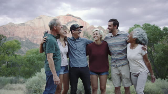 4K UHD:  Adults of All Ages Enjoying Southern Utah A group of young adults and seniors in a group hug while they chat and laugh with each other. The beautiful Utah landscape is in the background group of people stock videos & royalty-free footage