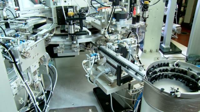 vídeos de stock, filmes e b-roll de linha de produção industrial avançada para as peças pequenas, trabalho robótico dos braços - equipamento médico