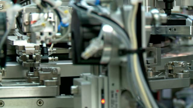 Advanced industrial production line for small parts, robotic arms working