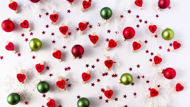 adventskalendernummern auf roten herzen beetwen dekorative schneeflocken und weihnachtskugeln - advent stock-videos und b-roll-filmmaterial