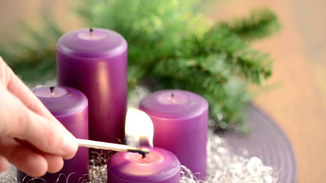 Advent con una corona de quemar velas y púrpura - vídeo