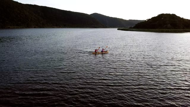 Adventurous couple paddling on the lake An adventurous couple enjoy an early morning paddle on the lake, they are on a yellow sea kayak western cape province stock videos & royalty-free footage