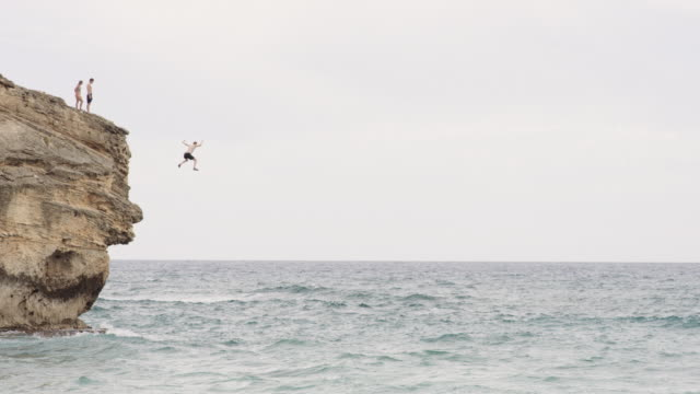 Adventurous man jumps off cliff into ocean Adventurous man jumps off of high cliff into ocean cliff jumping stock videos & royalty-free footage