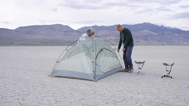 äventyrliga seniorer inrätta ett tält - aktiva pensionärer utflykt bildbanksvideor och videomaterial från bakom kulisserna