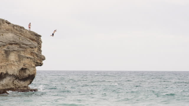 adventurous teen leaps off cliff into ocean - rischio video stock e b–roll