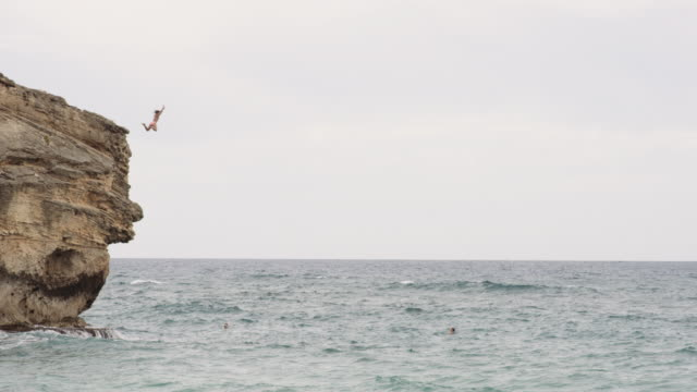 Adventurous woman jumps off cliff into ocean Adventurous woman jumps off cliff into rough ocean water cliff jumping stock videos & royalty-free footage