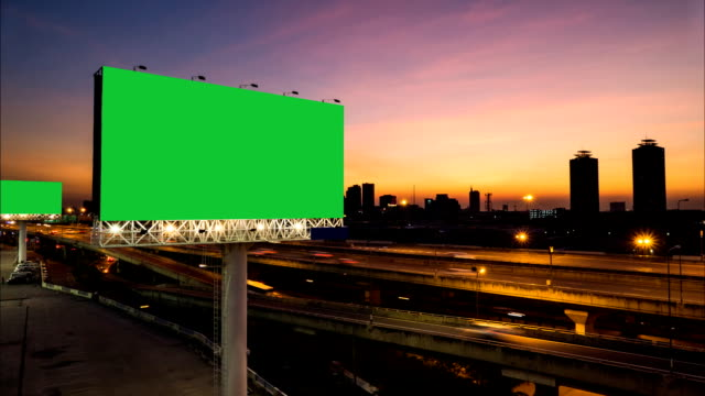 Advertising billboard green screen on sidelines of expressway. Advertising billboard green screen on sidelines of expressway with traffic at evening, time lapse. billboard stock videos & royalty-free footage