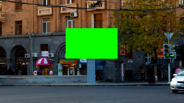 TIME LAPSE VIDEO. Advertising Billboard with green screen with long exposure cars in city, against backgrounds buildings with balconies, windows and signs shops. Camera moves away